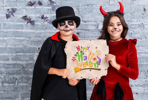 Irmãos, mostrando um cartão de feliz dia das bruxas plano médio