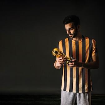 Jogador de futebol, olhando troféu