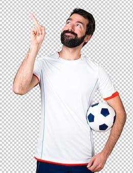 Jogador de futebol, segurando uma bola de futebol apontando para cima