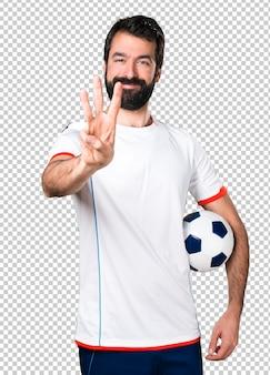 Jogador de futebol, segurando uma bola de futebol, contando com três