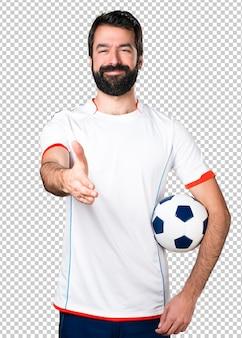 Jogador de futebol segurando uma bola de futebol fazendo um acordo