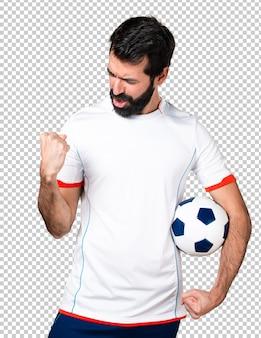 Jogador de futebol sorte segurando uma bola de futebol