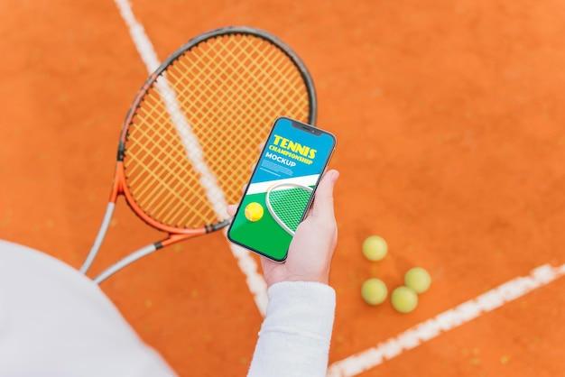 Jogador de tênis mostrando a tela do telefone