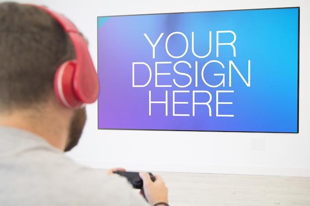 Jogador jogando videogame na televisão simulada