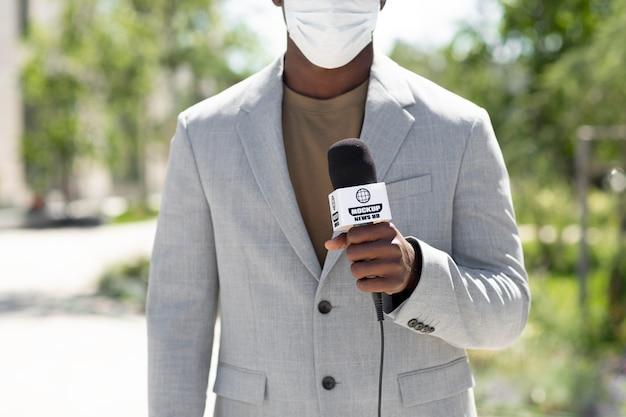 Jornalista segurando uma maquete de microfone