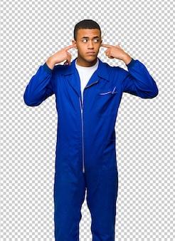 Jovem, afro americano, trabalhador, homem, cobertura, ambos, orelhas, com, mãos
