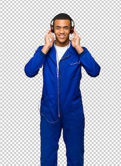 Jovem afro-americano trabalhador homem ouvindo música com fones de ouvido