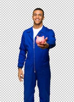 Jovem afro americano trabalhador homem segurando um piggybank