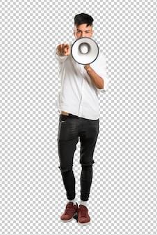 Jovem árabe com camisa branca gritando através de um megafone