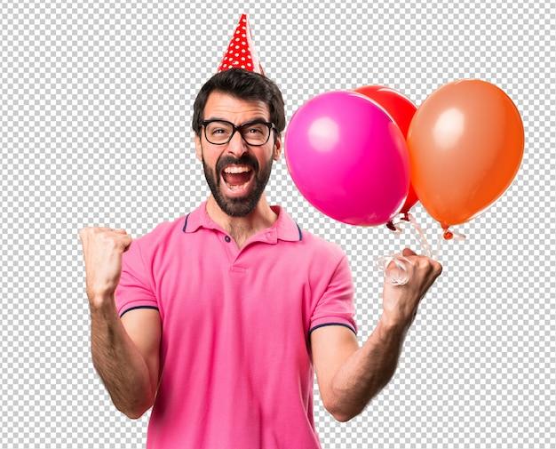 Jovem bonito afortunado segurando balões