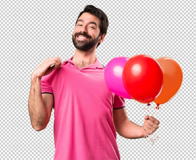 Jovem bonito segurando balões e orgulhoso de si mesmo