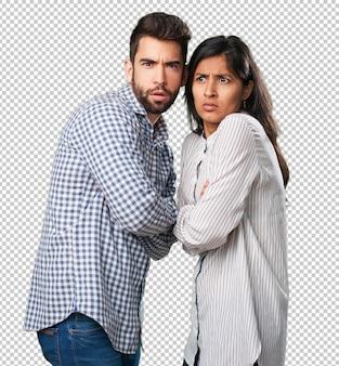 Jovem casal assustado em branco