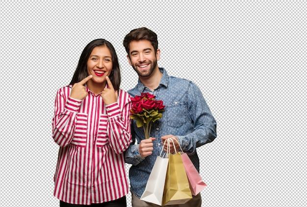 Jovem casal em dia dos namorados sorri, apontando a boca