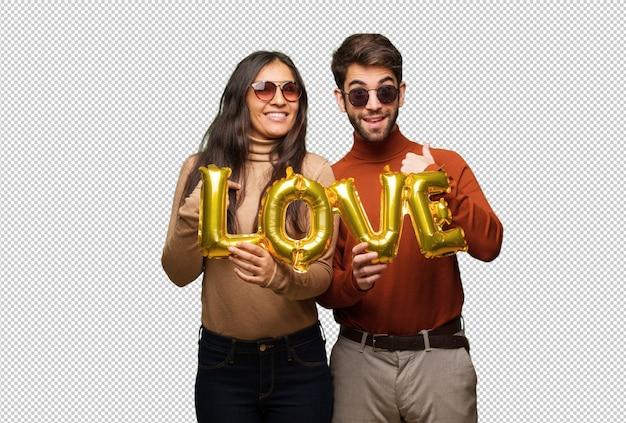 Jovem casal em dia dos namorados surpreso, sente-se bem sucedido e próspero