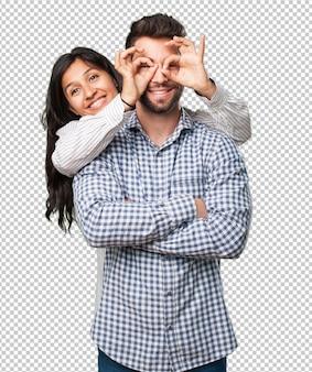 Jovem casal fazendo um gesto de óculos