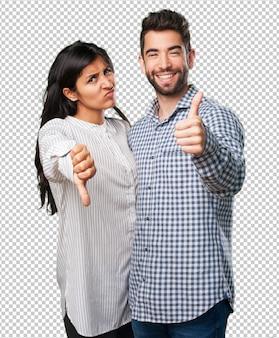 Jovem casal fazendo um símbolo contraditório
