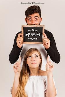 Jovem casal mostrando ardósia
