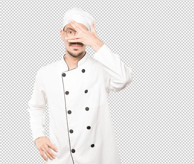 Jovem chef cobrindo os olhos com as mãos