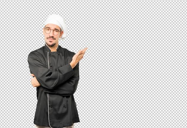 Jovem chef confuso, fazendo um gesto de não entender