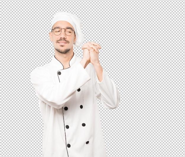Jovem chef fazendo um gesto de equipe trabalhar com as mãos