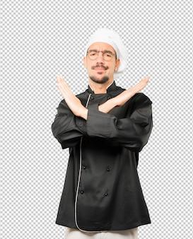 Jovem chef fazendo um gesto de não cruzar com os braços