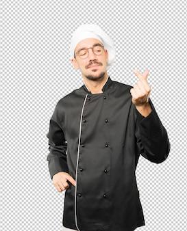 Jovem chef fazendo um gesto de preocupado com sua economia