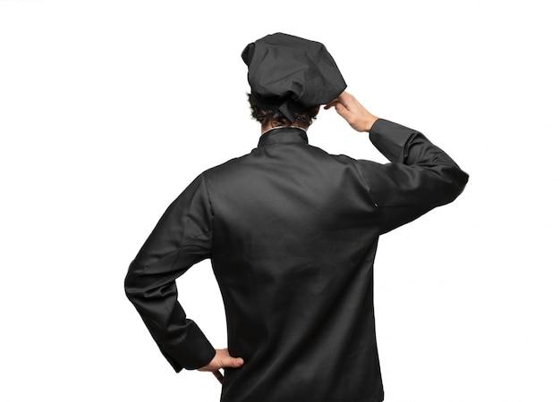 Jovem chef vista traseira, mão no quadril e coçar a cabeça com a outra mão