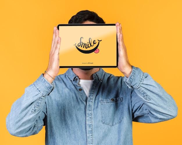 Jovem, cobrindo o rosto com um tablet simulado acima