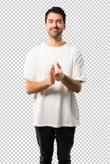 Jovem com camisa branca aplaudindo após apresentação em uma conferência