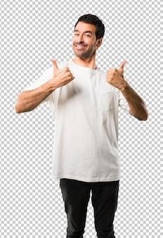 Jovem com camisa branca dando um polegar para cima gesto e sorrindo porque teve sucesso
