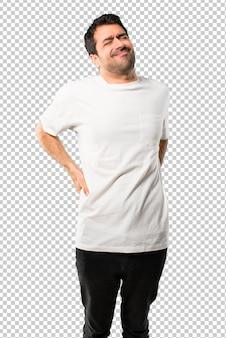 Jovem com camisa branca infeliz e sofrendo de dor nas costas por ter feito um esforço