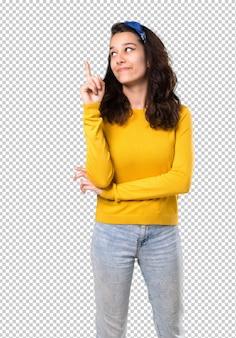 Jovem com suéter amarelo e bandana azul na cabeça apontando com o dedo indicador