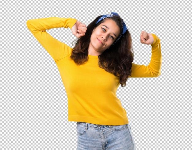 Jovem com suéter amarelo e bandana azul na cabeça dela gosta de dançar
