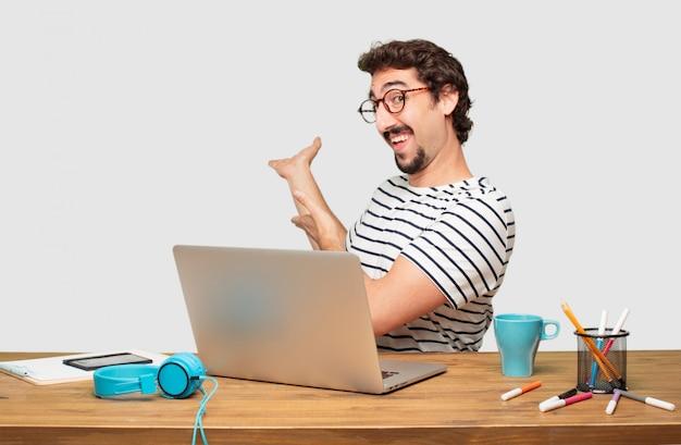 Jovem designer gráfico de barba com um laptop sorrindo com um olhar orgulhoso, satisfeito e feliz