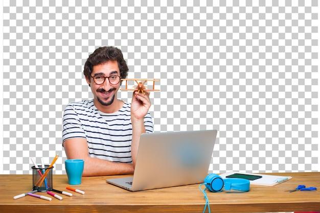 Jovem designer gráfico louco em uma mesa com um laptop e com um avião de madeira