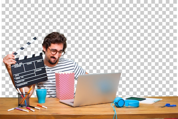 Jovem designer gráfico louco em uma mesa com um laptop e com um badalo de cinema