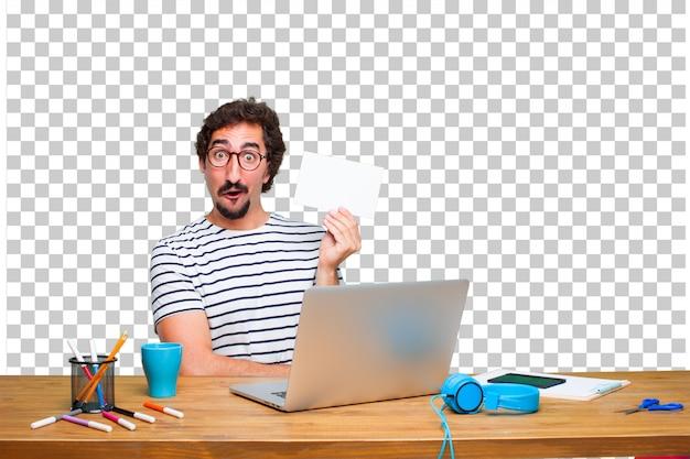 Jovem designer gráfico louco em uma mesa com um laptop e com um cartaz