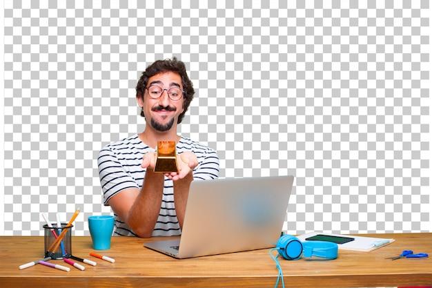 Jovem designer gráfico louco em uma mesa com um laptop e com um lingote de ouro
