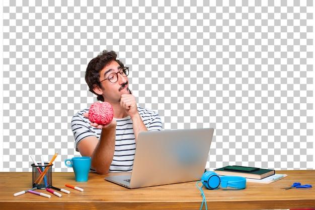 Jovem designer gráfico louco em uma mesa com um laptop e com um modelo de cérebro