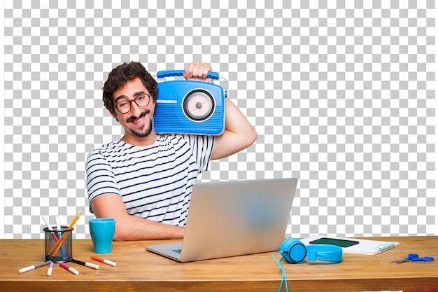 Jovem designer gráfico louco em uma mesa com um laptop e com um rádio vintage