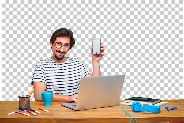 Jovem designer gráfico louco em uma mesa com um laptop e com um telefone de tela de toque inteligente