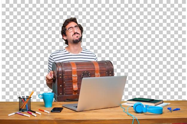 Jovem designer gráfico louco em uma mesa com um laptop e com uma caixa de pirata
