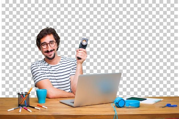 Jovem designer gráfico louco em uma mesa com um laptop e com uma câmera de cinema vintage