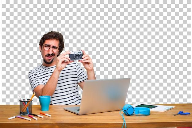 Jovem designer gráfico louco em uma mesa com um laptop e com uma câmera vintage