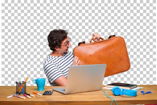 Jovem designer gráfico louco em uma mesa com um laptop e com uma maleta de couro