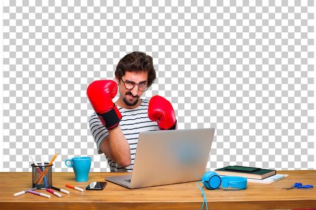 Jovem designer gráfico louco em uma mesa com um laptop e usando luvas de boxe