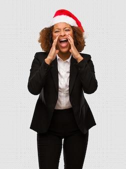 Jovem empresária preta vestindo um chapéu de papai noel de natal gritando algo feliz para a frente