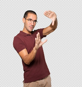 Jovem espantado fazendo um gesto de tirar uma foto com as mãos