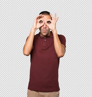 Jovem espantado usando as mãos como um binóculo