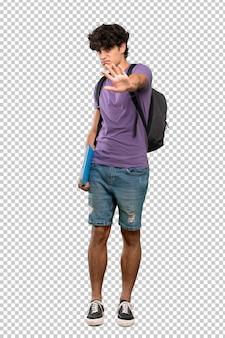 Jovem estudante homem nervoso esticando as mãos para a frente